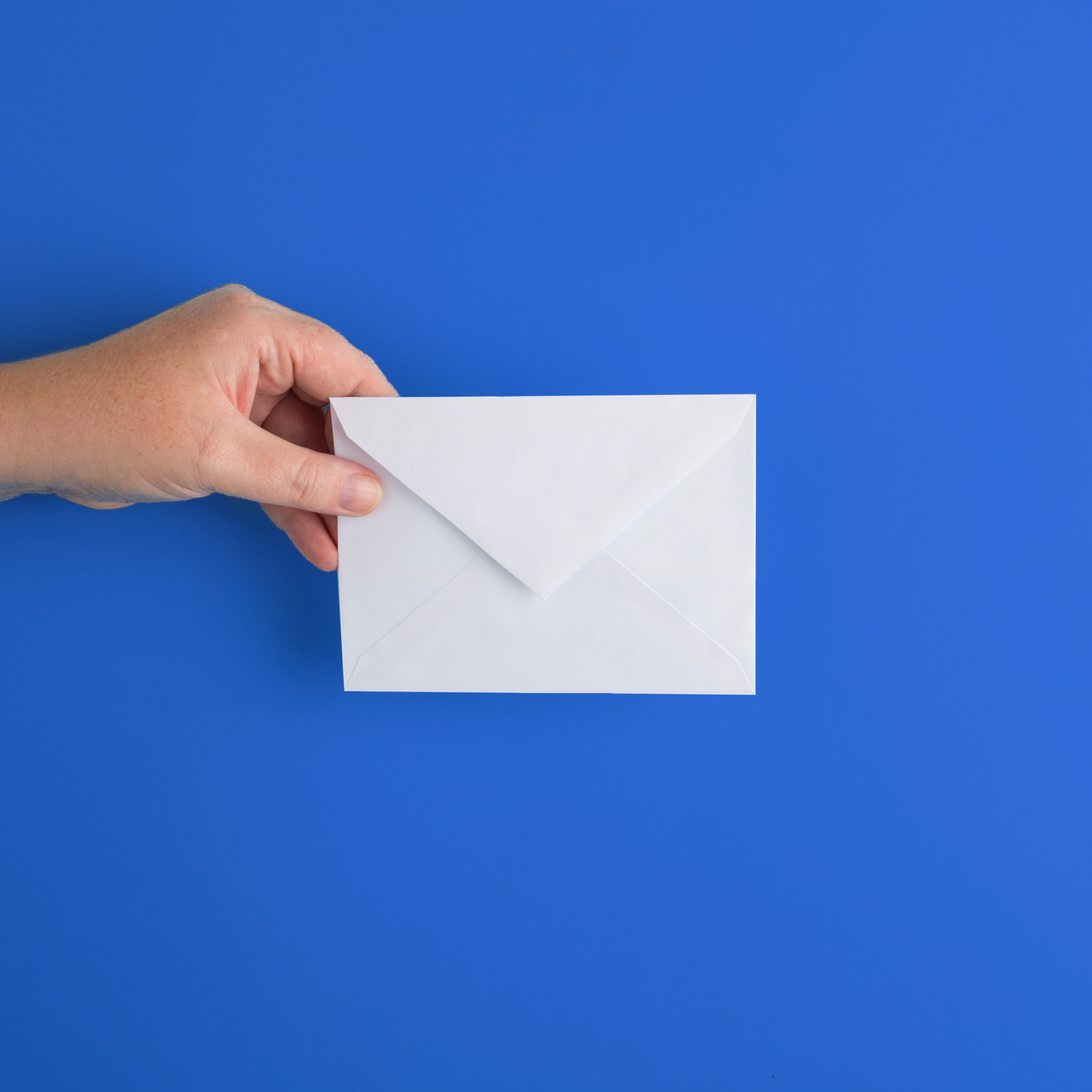 hand holding an envelope in front of a blue background