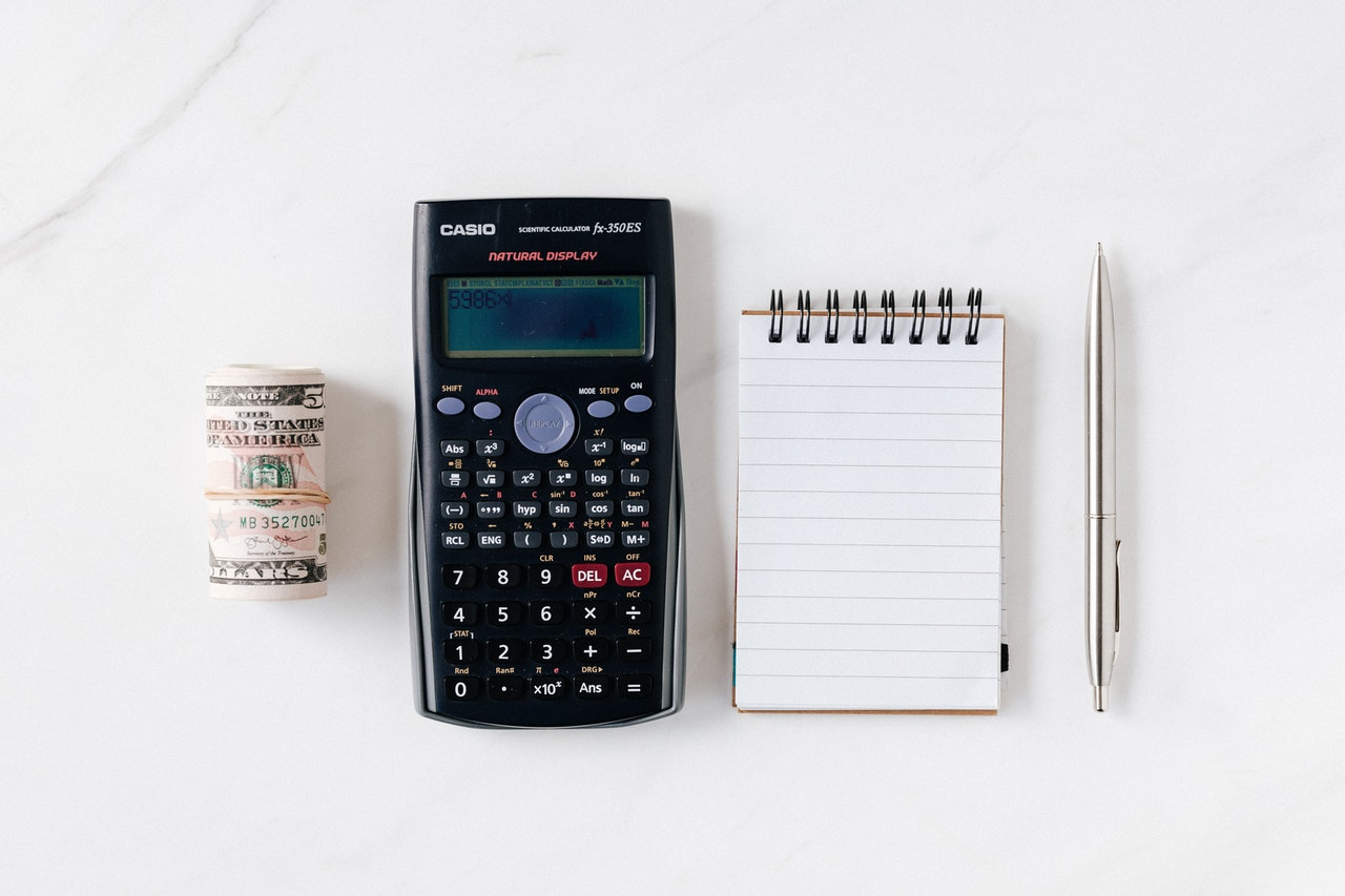 smartphone, money, notebook and pen on a table