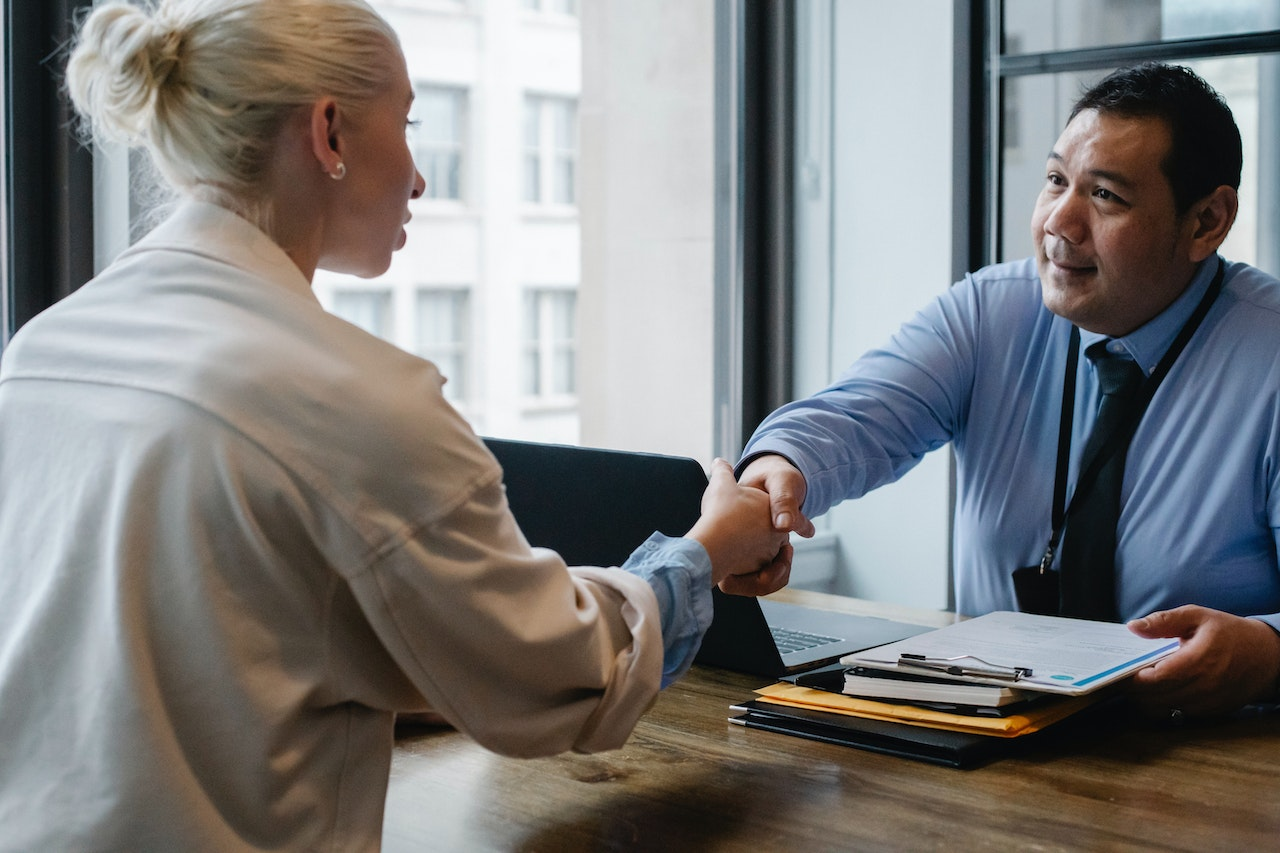 blonde business woman shaking hand of man in shirt and tie