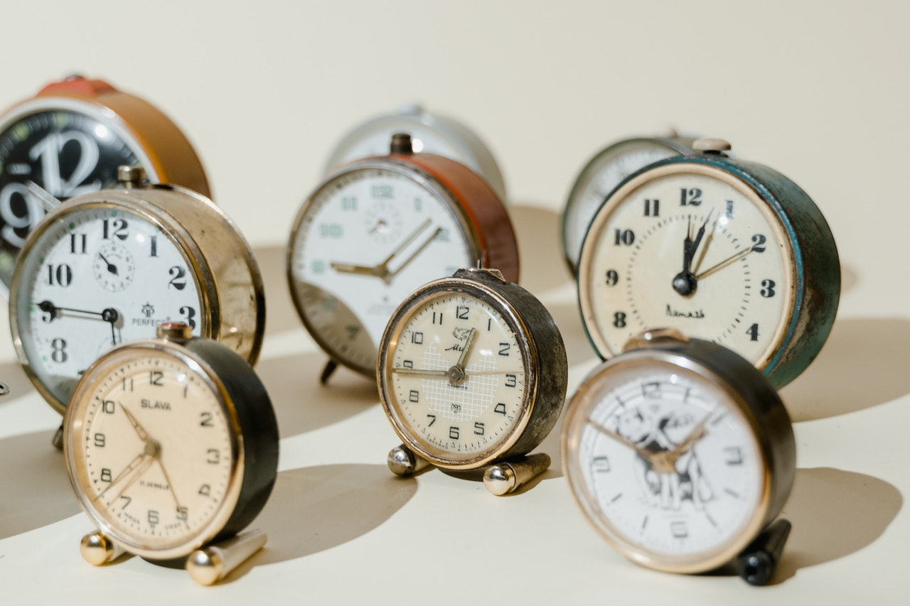 small clocks arranged on a beige background