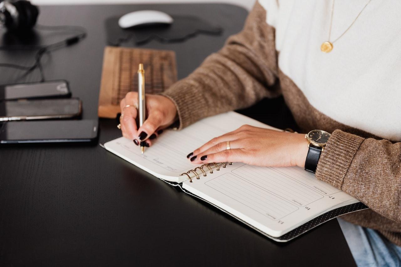woman writing in notebook wearing black nail polish