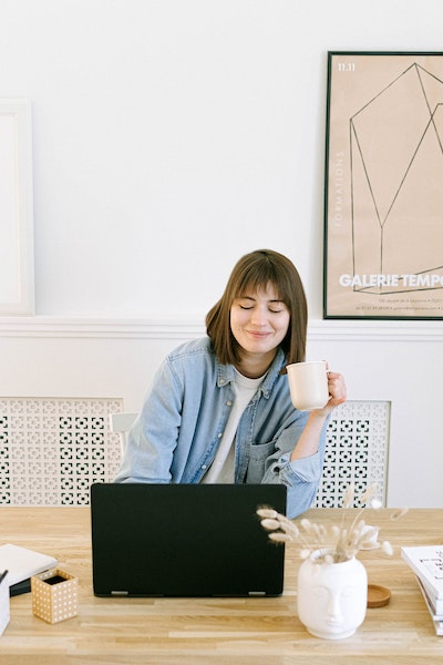 woman holding a mug and working in front of a black computer