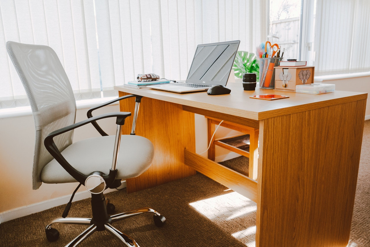 white office chair next to brown wooden work from home desk