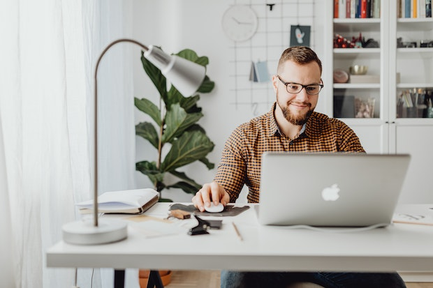 Man weairing glasses with a plant behind him smiling at a computer