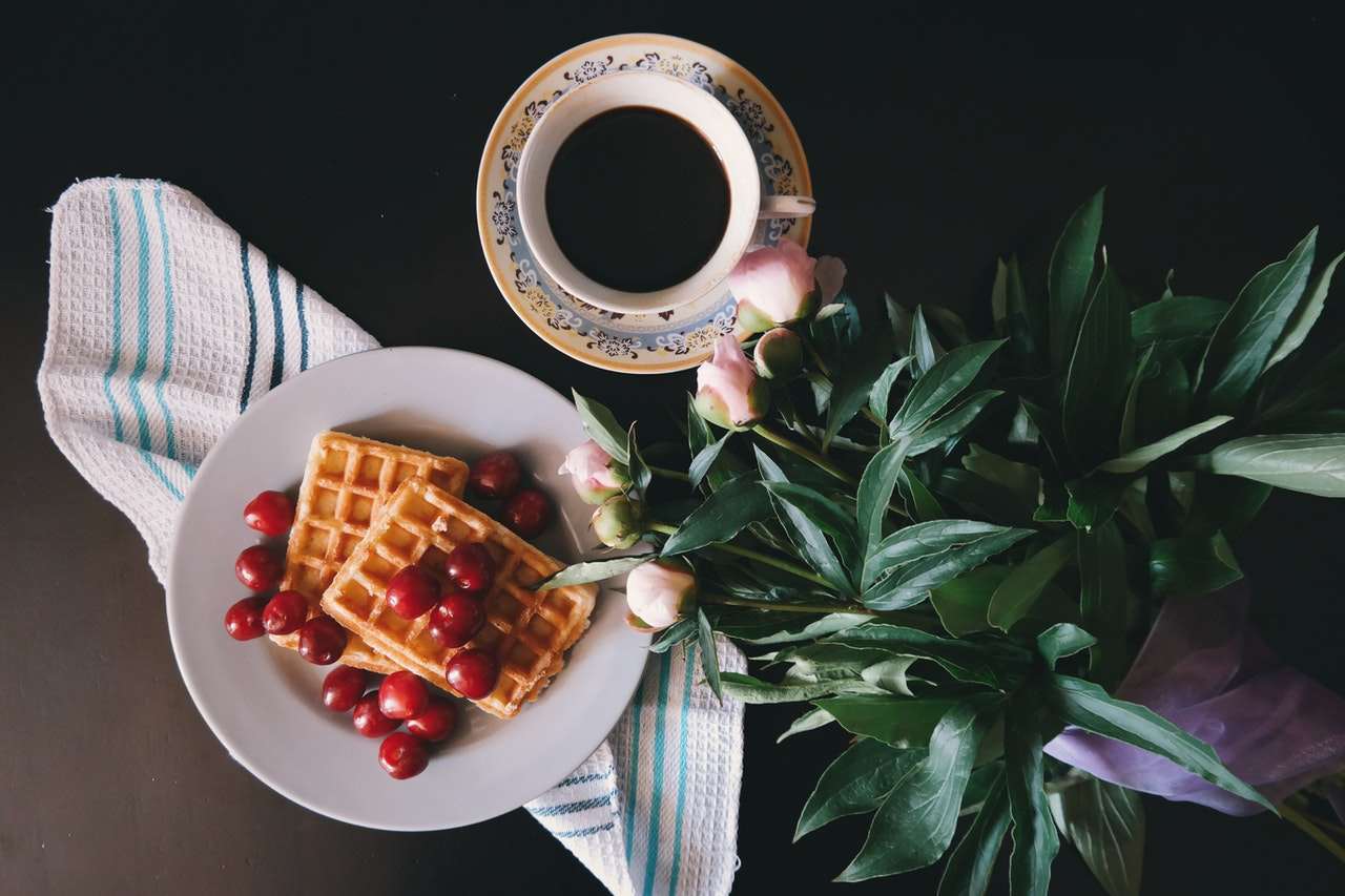 An aerialview of a very photogenic plate of waffles dotted with artfully arranged cherries. On the table next to it are pink peonies and a teacup.
